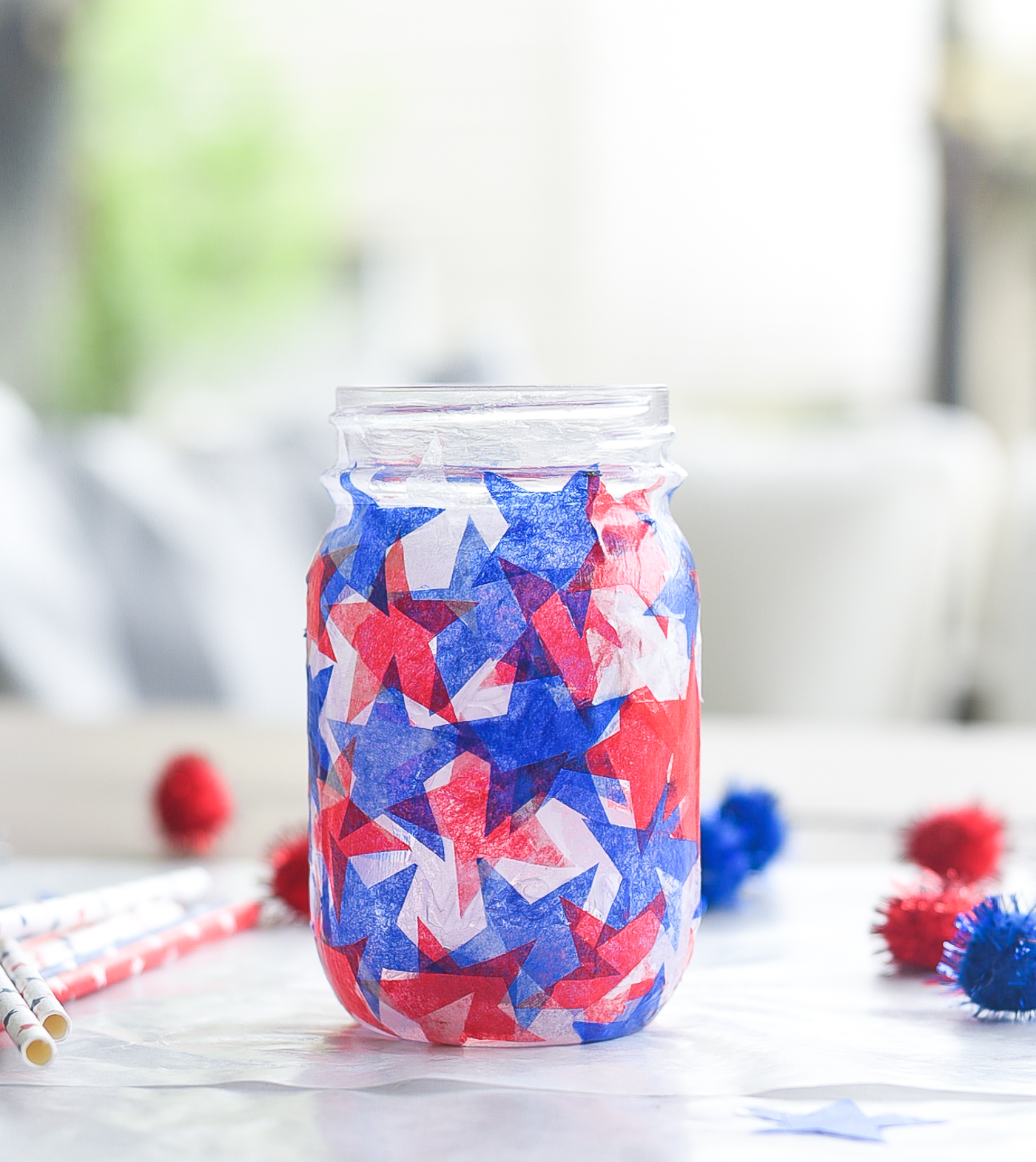 Tissue paper stained glass mason jar craft. Red white blue tissue paper craft. Mod Podge jar in red, white blue. Star shaped tissue paper decoupage mason.